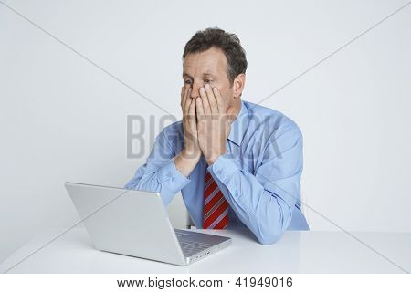 Depressed businessman covering his face while sitting with laptop