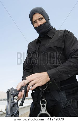 Commando standing with handgun on military training