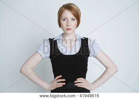 Confident young woman standing akimbo