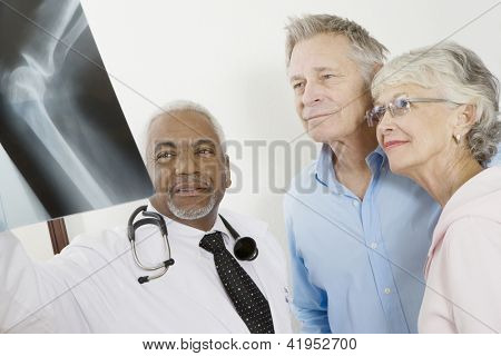 African American doctor showing analyzed x-ray to patients