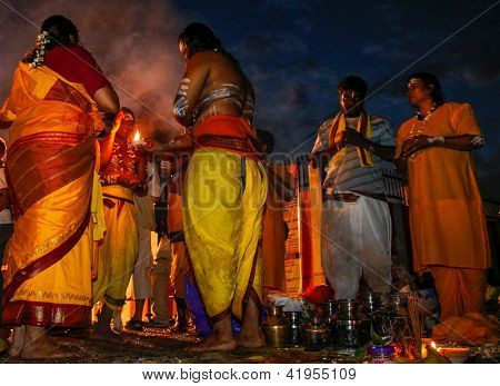 KUALA LUMPUR - JANUARY 27: A Hindu priest prays and blesses a family at dawn in preparation for their walk to the Batu Caves temple in Malaysia on January 27, 2013 during the Thaipusam festival.
