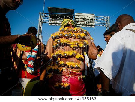 KUALA LUMPUR - JANUARY 27: A devotee with skin hooks pierced to his back as an act of devotion to Lord Muruga walks to the Batu Caves temple in Malaysia on January 27, 2013 at the Thaipusam festival.