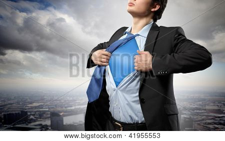Image of young businessman showing superhero suit underneath his shirt standing against city background