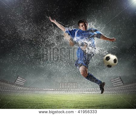 football player in blue shirt striking the ball aloft at the stadium under the rain