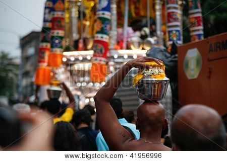 KUALA LUMPUR - JANUARY 26: Hindu devotees carry milk pots or 'pal kodum' as offerings to Lord Muruga walk to the Batu caves temple in Malaysia on January 26, 2013 during the Thaipusam festival.