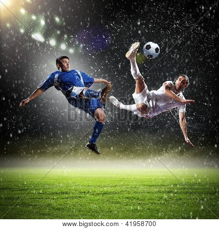 two football players in jump to strike the ball at the stadium under rain
