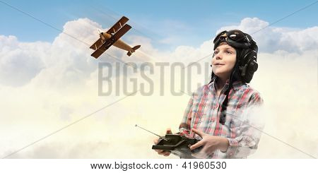 Image of little boy in pilots helmet playing with toy radiocontrolled airplane against clouds background