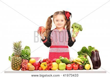 A smiling girl with apron holding a broccoli and red apple behind a table full of fruits and vegetables isolated on white