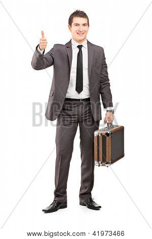 Full length portrait of a young businessman holding a briefcase and giving thumb up isolated on white background