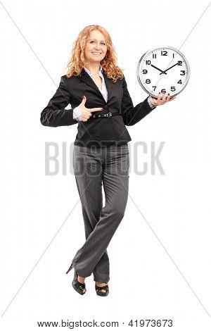 Full length portrait of a blond mature woman standing and pointing on a wall clock, isolated on white background
