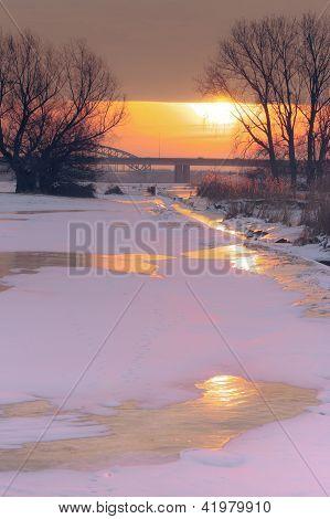 Winterliche Auen mit Reed und Banken gegen wolkenschleier Sonnenuntergang-Himmel