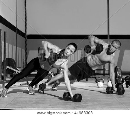 Gym man and woman push-up strength pushup with dumbbell in a workout