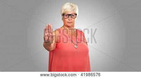 Portrait Of A Senior Woman Showing Stop Sign On Gray Background