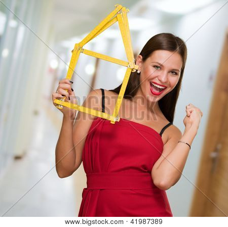Woman Holding House Frame doing a success gesture in a passage way