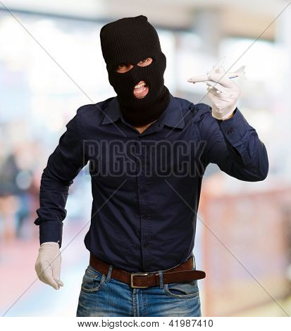 Man wearing robber mask and holding airplane miniature, outdoor