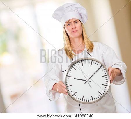 Female Chef Holding Clock against an abstract background