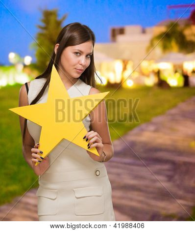 Portrait Of Young Woman Holding Yellow Star, outdoor