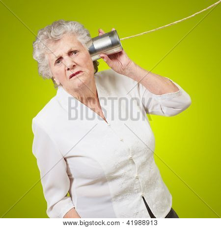 Portrait of a senior woman hearing with metal tin on green background