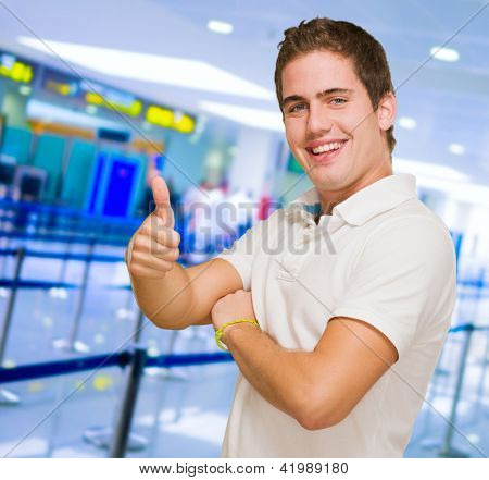 Young Man Showing Thumb Up at an airport