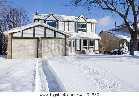 House and Driveway Covered with Fresh Snow
