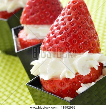 strawberries filled with cream in cubical black bowls