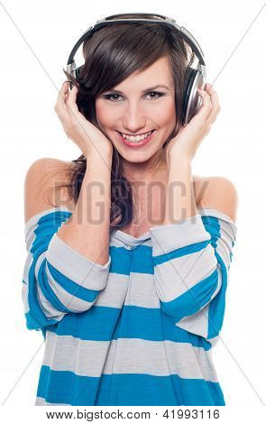 Smiling female listening music through headphones isolated on white