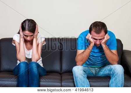 Couple sitting in a sofa mad at each other