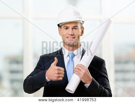 Engineer in white hard hat hands layout and thumbs up. Concept of successful construction