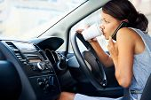 stock photo of takeaway  - Businesswoman multitasking while driving - JPG