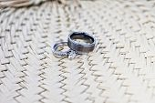 pair of wedding rings on thatch background