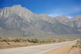 foto of mt whitney  - Empty road leading to slightly snow spotted Mt - JPG