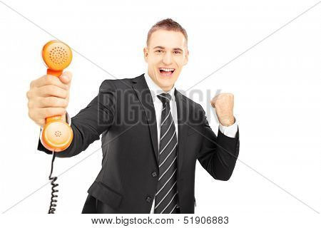Young man in suit holding a telephone tube and smiling isolated on white background