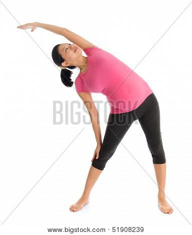 Prenatal yoga class. Full length healthy Asian pregnant woman doing yoga exercise stretching, full body isolated on white background. Yoga positions standing side stretch.