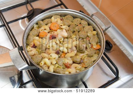 Saucepan digested soup and swollen pasta stands on a gas stove