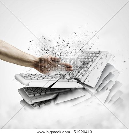Image of human hand breaking pile of keyboards