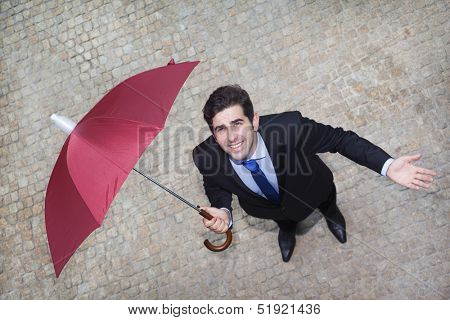 Confident businessman looking to the sky and checking if it's raining