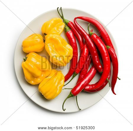 top view of chili peppers and habanero on plate on white background