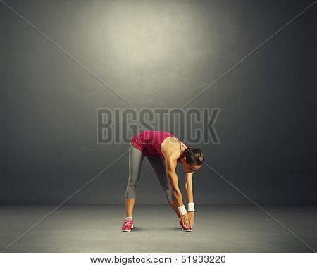 young sporty woman doing exercises over dark background