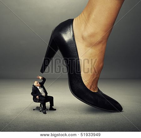 concept photo of senior man under big female heel