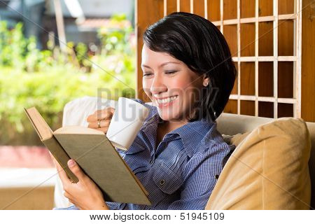Student - Young asian woman or girl sitting on a sofa with a cup of coffee reading a book, she is learning