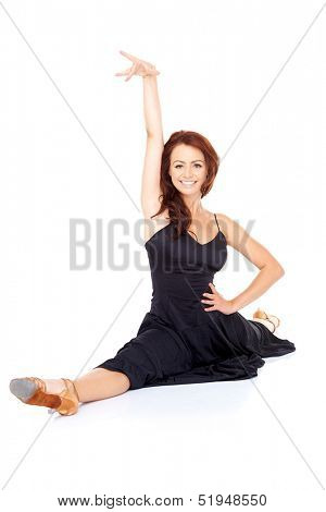 Beautiful supple fashionable woman doing the splits in a black cocktail dress and high heels and smiling at the camera as she strikes a pose over a white background