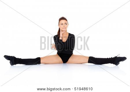 Supple young woman in a leotard and leggings doing the splits and smiling happily at the camera over a white background