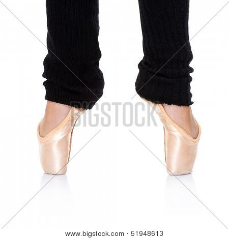 Close up view of a ballerina in ballet shoes and leggings practising ballet feet positions standing en pointe