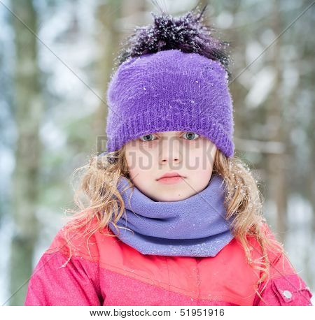 Little Blond Girl In Winter Outwear With Snowflakes Above Forest Background