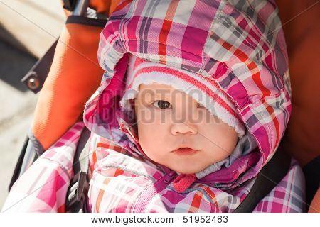 Little Baby Girl In Warm Outwear Seats In Pram On The Walk