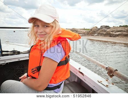 Little Girl On A Small Boat Wears Bright Orange Life-jacket