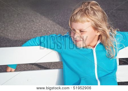 Little Blond Girl In Casual Sport Outwear Relaxes With Smile On White Park Bench