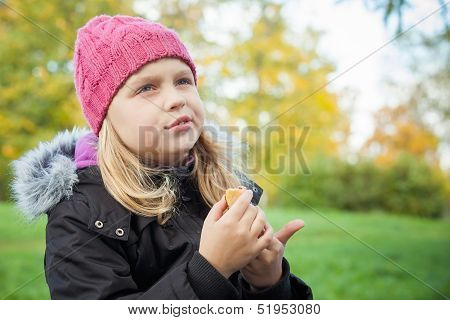 Little Beautiful Blond Girl Eating Cake And Thinking About Something. Outdoor Portrait.