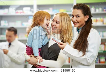 Cheerful pharmacist chemist woman demonstrating vitamins to child girl in pharmacy drugstore