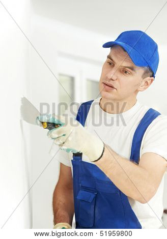 Plasterer home improvement handyman worker with putty knife working on apartment wall filling